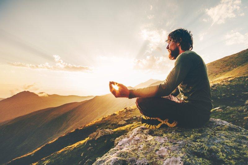 Muž meditujúci v prírode.