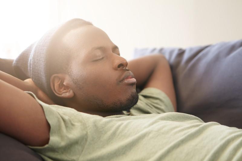 Muž spiaci na gauči.